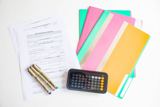 Calculator, folders, paper and pens on a work desk